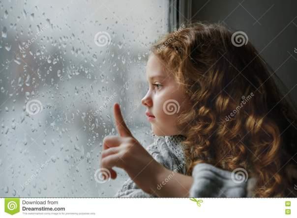 la-petite-fille-triste-regardant-la-fentre-sur-la-pluie-se-laisse-tomber-prs-du-gl-humide-78494679